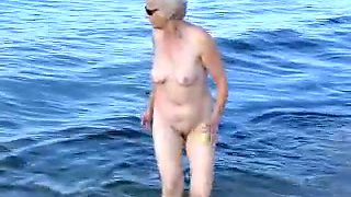 Naked old woman playing and having fun on the beach