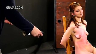Kinky, red haired babe got tied up to a chair and forced to suck various sex toys