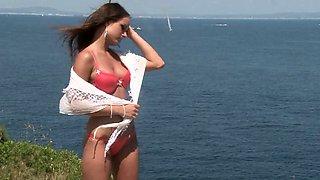 Gorgeous brunette removes her bikini on the beach