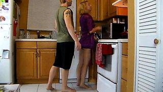Busty milf teases and pleases her young lover in the kitchen