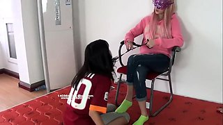 Masked blonde dominates a lovely Asian babe with her feet